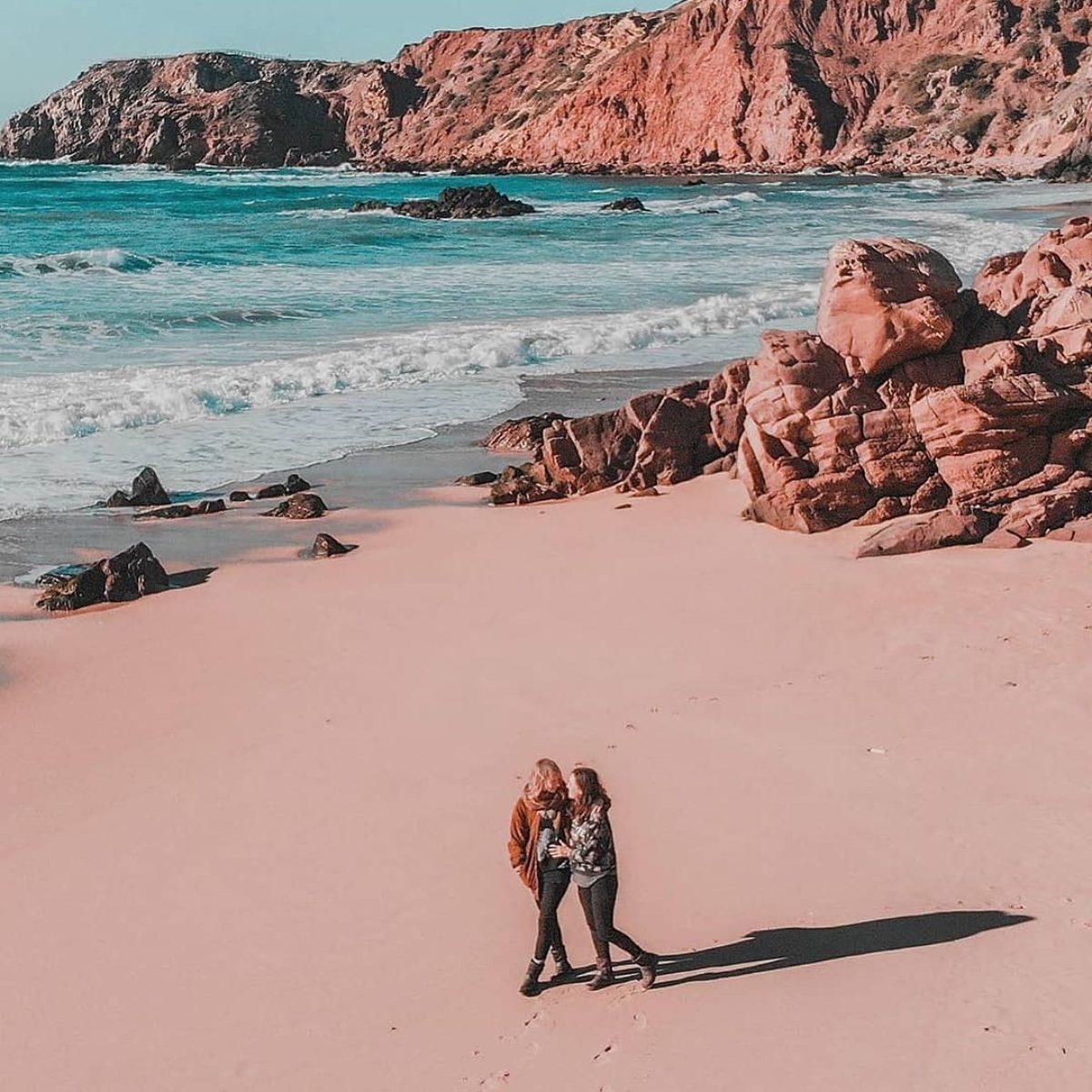 Couple of women walking in the beach near the seashore, Portugal
